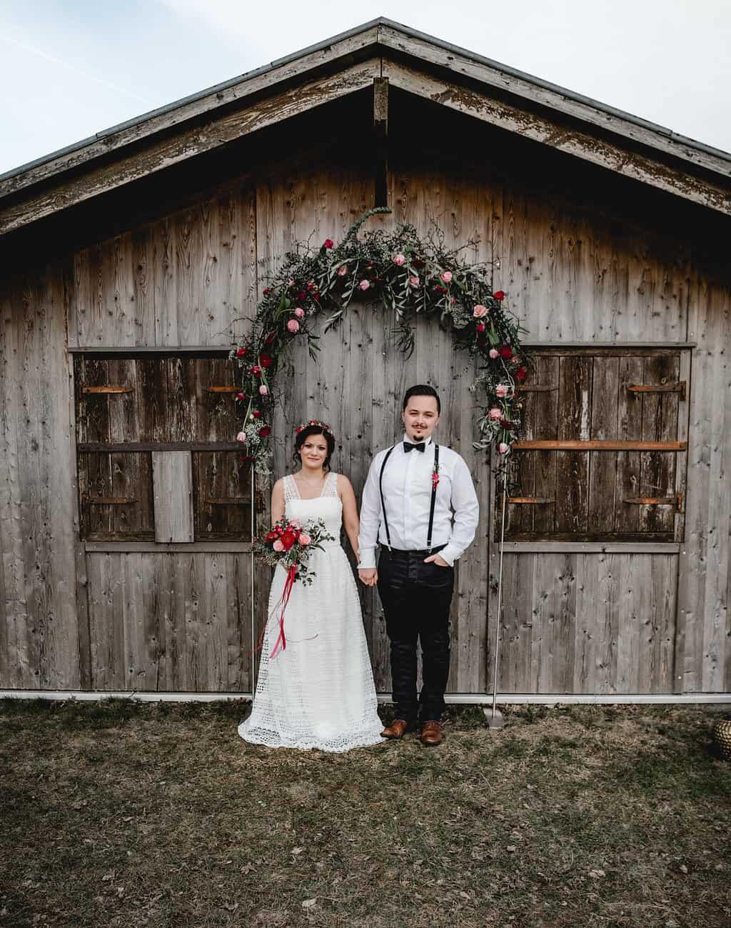 Hochzeitsinspiration Red Velvet, Brautpaar unter Blumenbogen | marygoesround.de