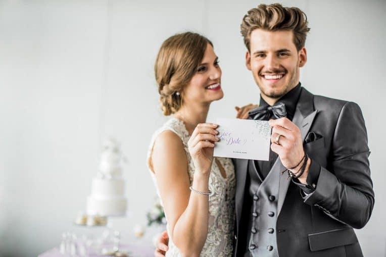 Hochzeitsinspiration: Grau küsst Lila (Zürichsee), Brautpaar mit Save-the-Date-Karte | marygoesround.de